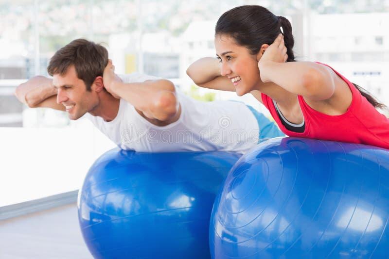Pares aptos que ejercitan en bolas de la aptitud en gimnasio imagen de archivo