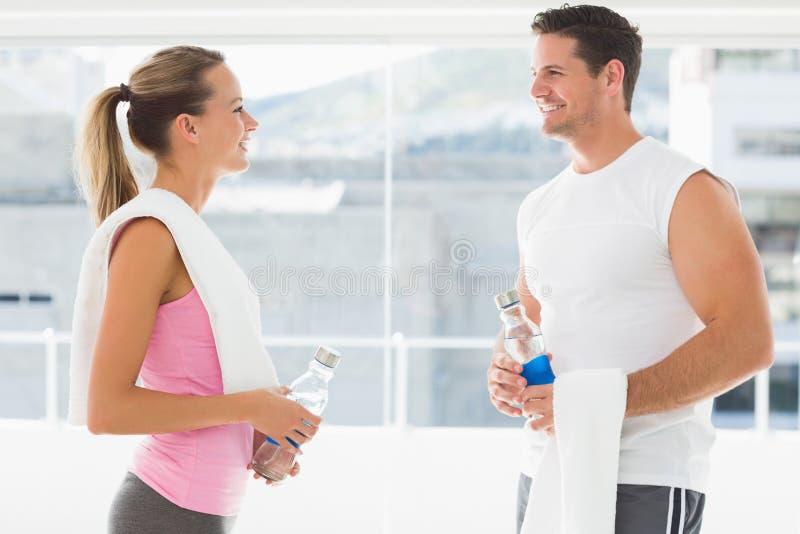 Pares aptos que guardam garrafas de água e toalhas na sala de exercício foto de stock royalty free