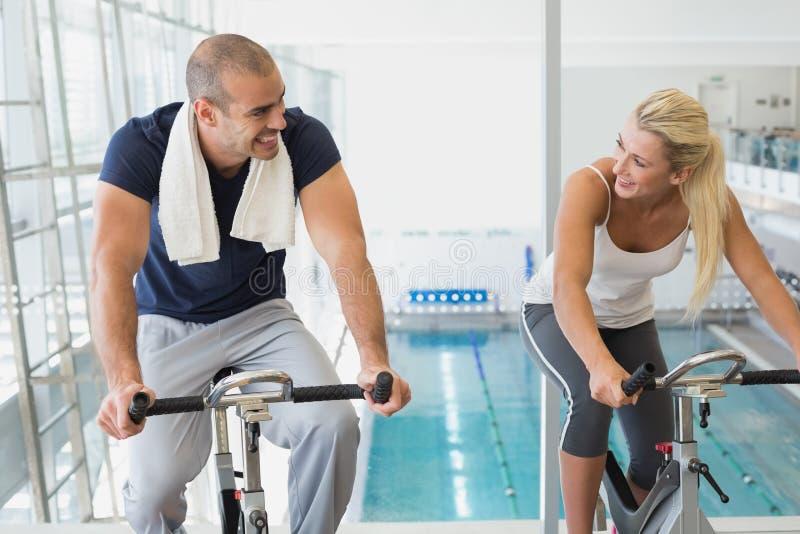 Pares aptos que trabalham em bicicletas de exercício no gym fotos de stock