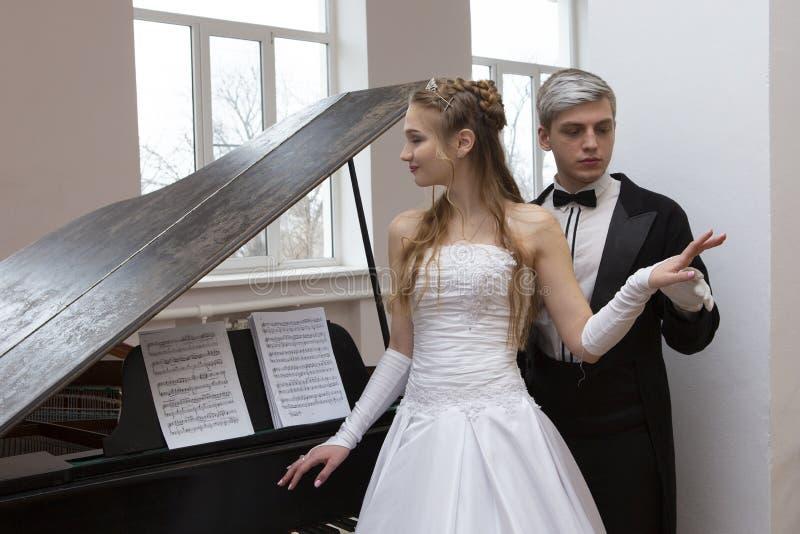Pares apuestos jovenes en vestido de noche y capa de vestido que presenta de manera elegante en un estilo clásico imagenes de archivo