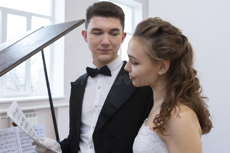 Pares apuestos jovenes en vestido de noche y capa de vestido que presenta de manera elegante en un estilo clásico foto de archivo libre de regalías