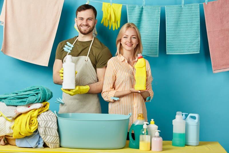 Pares apuestos positivos que sostienen las botellas detergentes fotos de archivo