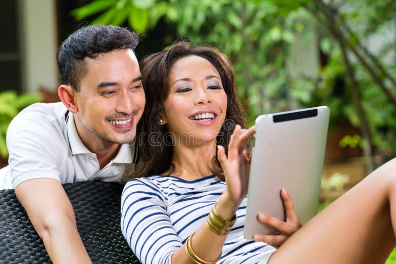 Pares asiáticos al aire libre con una PC de la tableta fotografía de archivo libre de regalías