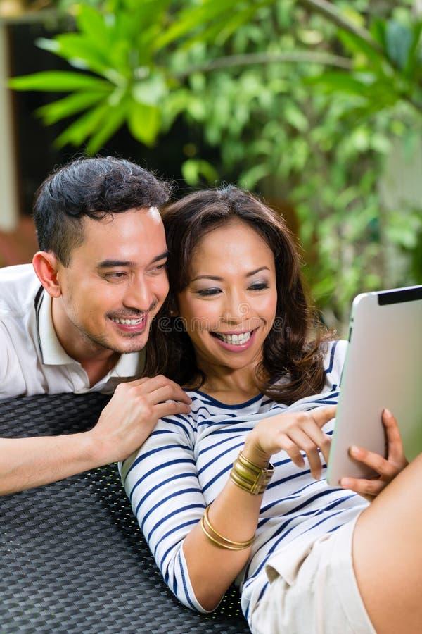 Pares asiáticos al aire libre con una PC de la tableta foto de archivo