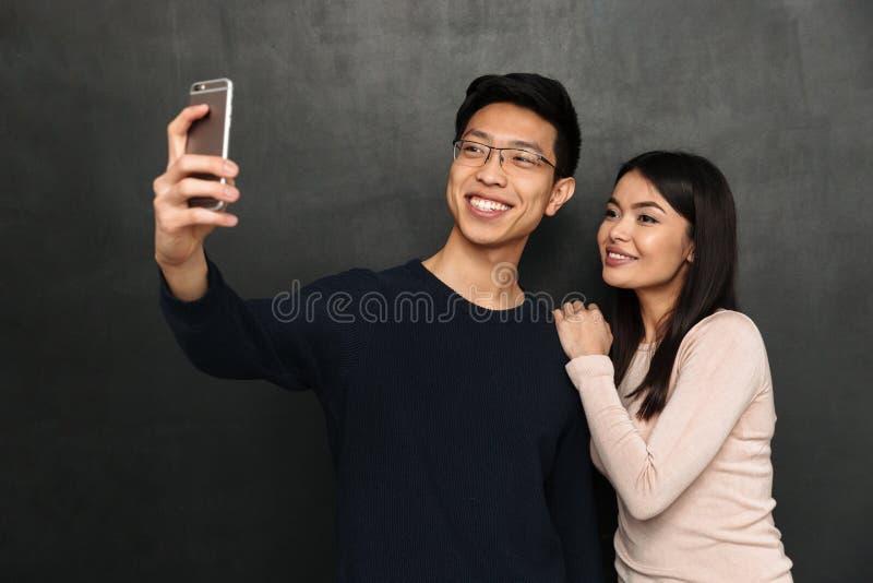 Pares asiáticos alegres que presentan junto y que hacen el selfie en smartphone imagen de archivo libre de regalías