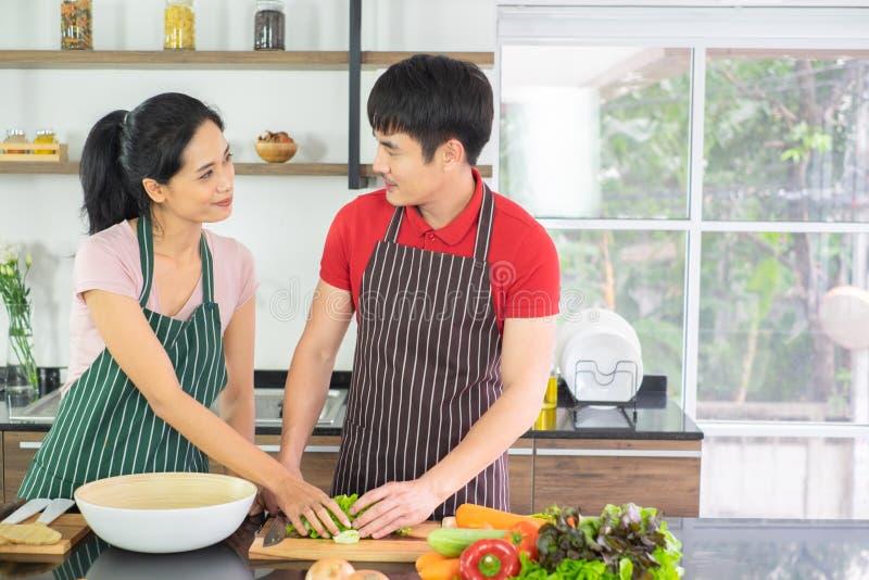 Pares asiáticos Ambos olham os olhos de cada um cozinhando assim o divertimento junto na cozinha com o completo do ingrediente na imagem de stock royalty free