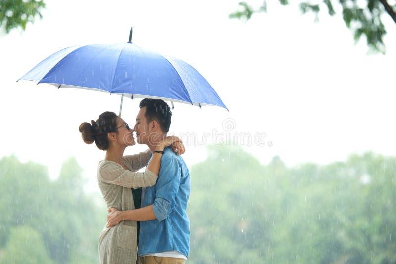Pares asiáticos cariñosos en lluvia debajo del paraguas imagen de archivo libre de regalías