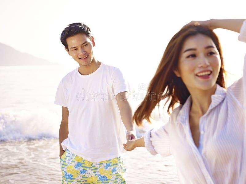 Pares asiáticos cariñosos jovenes en la playa foto de archivo