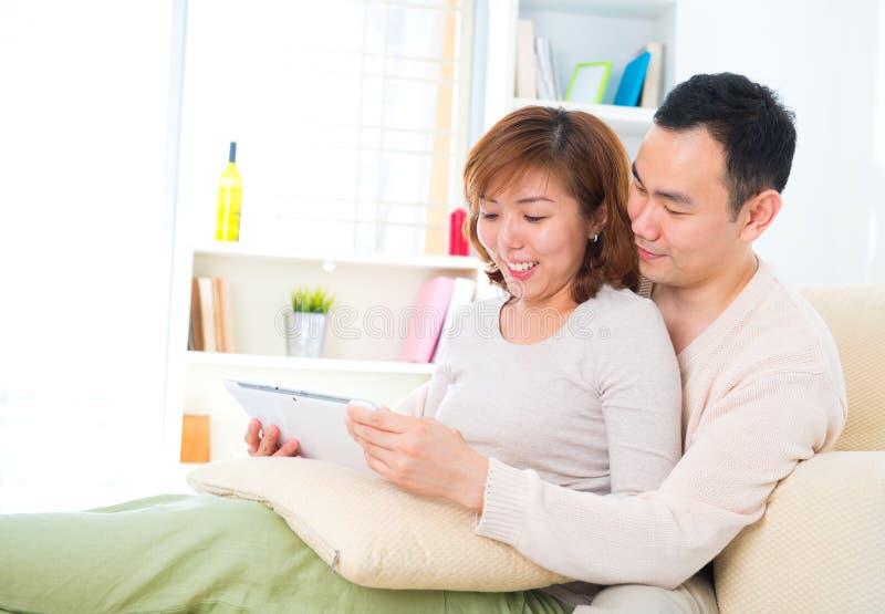 Pares asiáticos com o computador digital da tabuleta imagem de stock royalty free