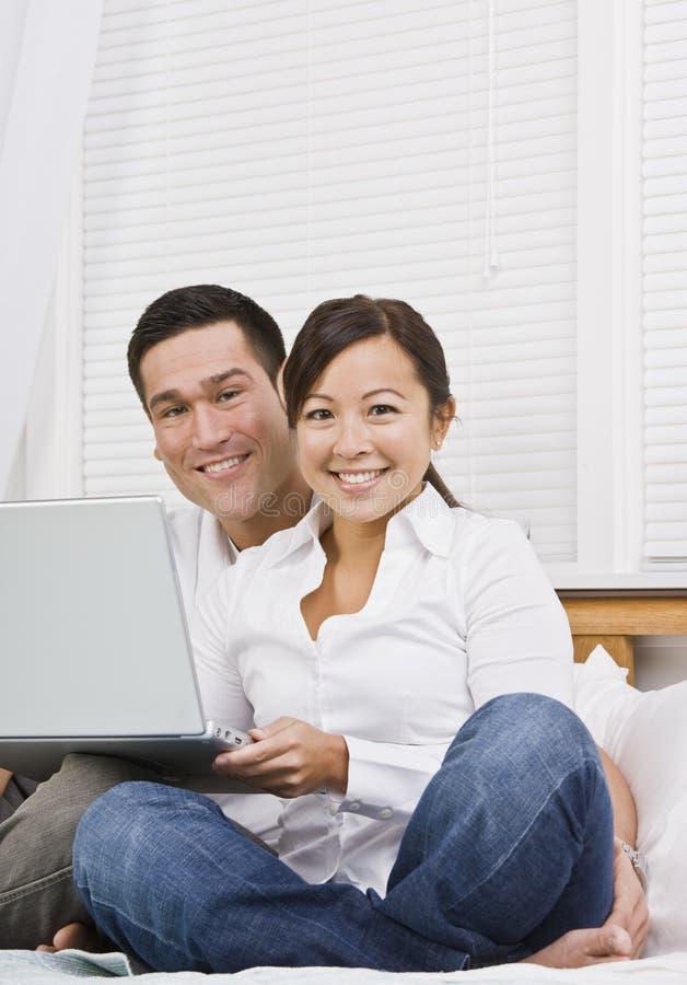 Pares asiáticos con la computadora portátil fotos de archivo