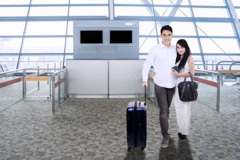 Pares asiáticos con la maleta que sonríe en terminal de aeropuerto fotografía de archivo libre de regalías