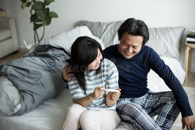 Pares asiáticos con la prueba embarazada fotos de archivo
