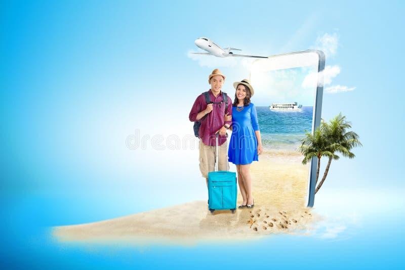Pares asiáticos con la situación del bolso y de la mochila de la maleta en la playa foto de archivo libre de regalías