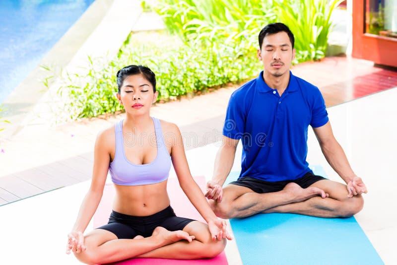 Pares asiáticos de la yoga en la mediación del asiento del loto fotos de archivo libres de regalías
