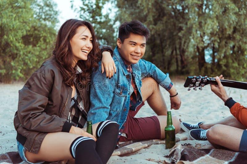 Pares asiáticos de sorriso que sentam-se no Sandy Beach e que escutam seu amigo que joga a guitarra imagem de stock royalty free