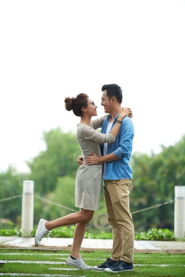 Pares asiáticos despreocupados que abraçam na data imagem de stock royalty free