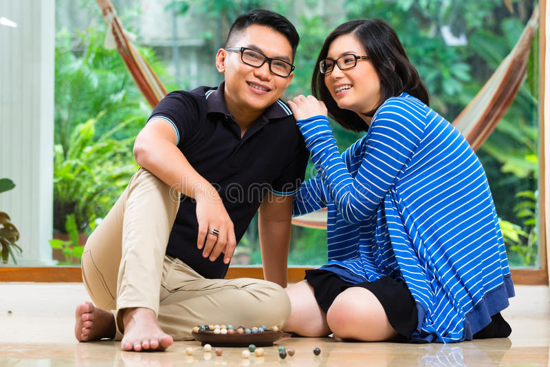 Pares asiáticos em casa que jogam com mármores fotografia de stock royalty free