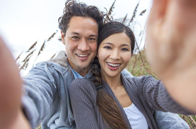 Pares asiáticos en la playa que toma la fotografía de Selfie imágenes de archivo libres de regalías