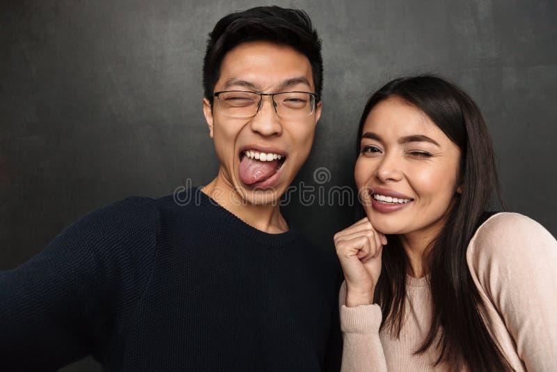 Pares asiáticos felices divertidos que presentan junto y que hacen el selfie imagenes de archivo