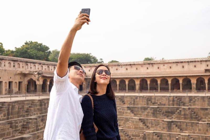 Pares asiáticos felices en el amor que toma la foto del selfie en el stepwell de Chand Baori en la India fotos de archivo libres de regalías