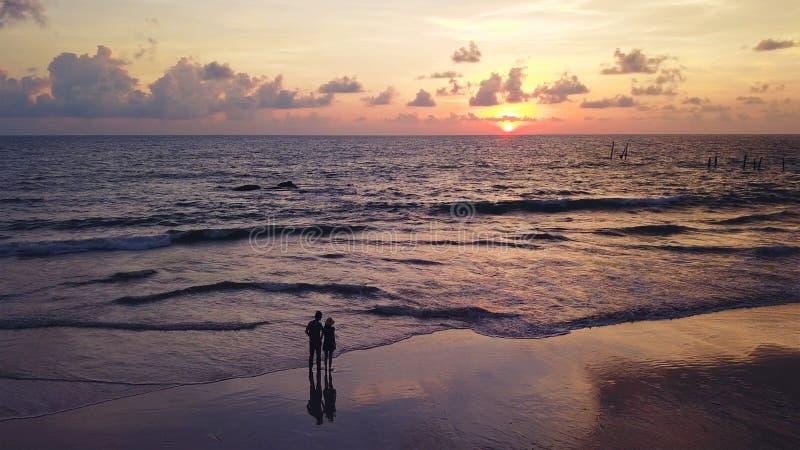 Pares asiáticos felices que fechan en la playa durante viaje de la luna de miel del viaje el vacaciones de los días de fiesta al  imagen de archivo libre de regalías