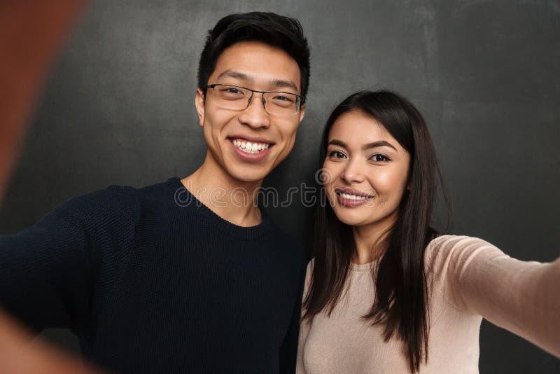 Pares asiáticos felices que presentan junto y que hacen el selfie imágenes de archivo libres de regalías