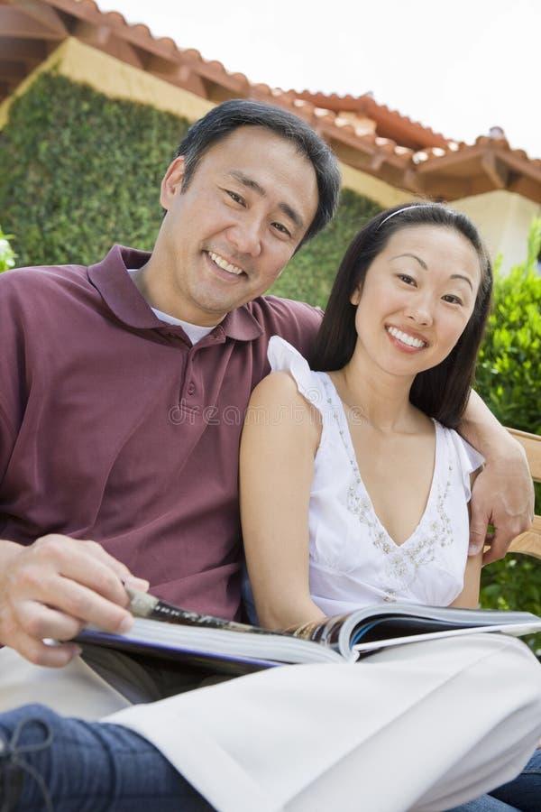 Pares asiáticos felizes com novela imagem de stock royalty free