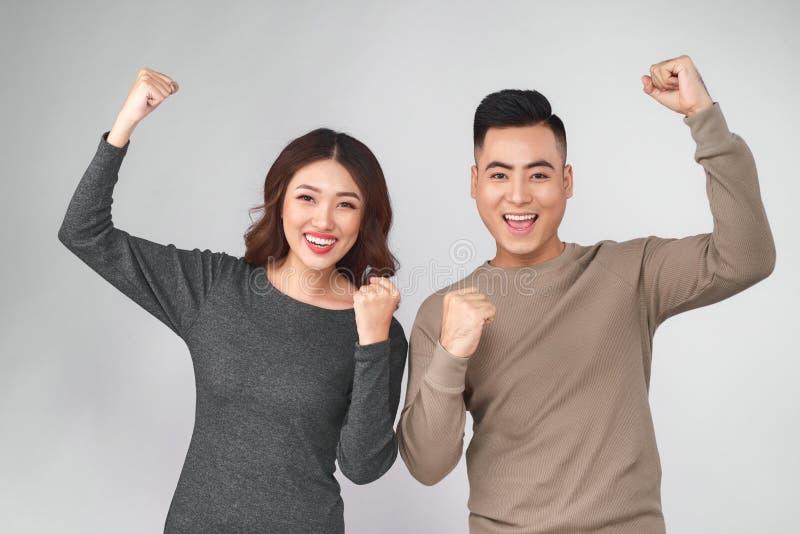 Pares asiáticos felizes de sorriso que mantêm ambos os polegares imagens de stock royalty free