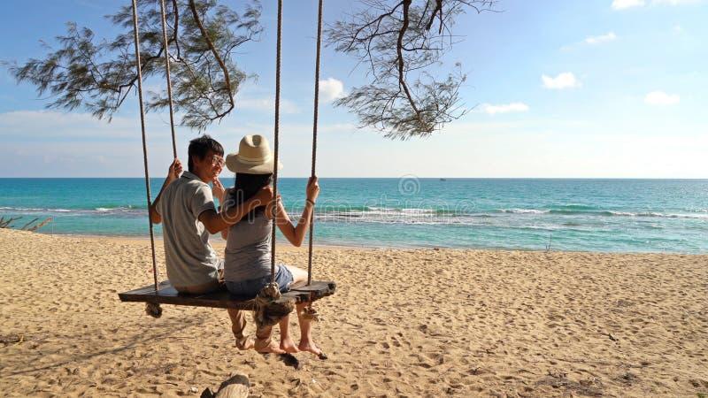 Pares asiáticos felizes que balançam em um balanço na praia durante a viagem do curso no ar livre das férias dos feriados no ocea imagens de stock