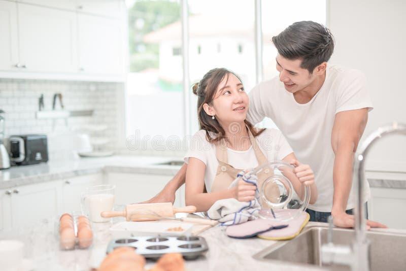 Pares asiáticos felizes que lavam os pratos após o café da manhã, refeição fotos de stock