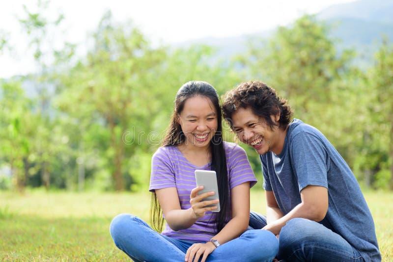 Pares asiáticos felizes que sentam-se na grama verde em exterior imagem de stock