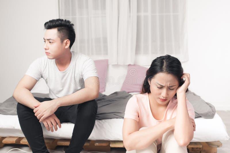Pares asiáticos infelices jovenes que se sientan de nuevo a la parte posterior en Sofa At Home imagen de archivo