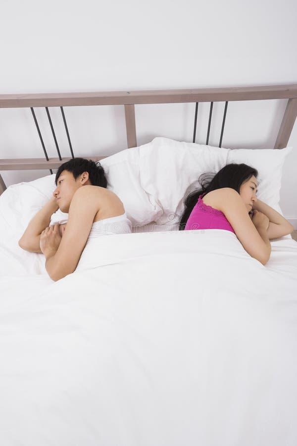 Pares asiáticos infelices que duermen de nuevo a la parte posterior en cama fotos de archivo libres de regalías