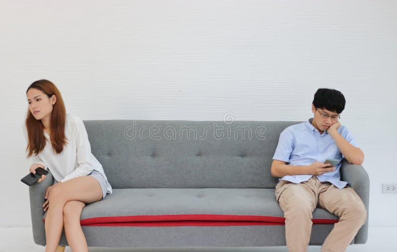 Pares asiáticos irritados infelizes que sentam-se afastado após o argumento na sala de visitas Conceito mau dos pares do relacion imagem de stock royalty free