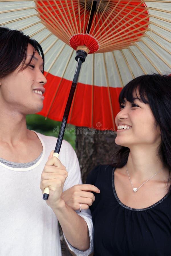 Pares asiáticos jovenes felices que sonríen con el paraguas imágenes de archivo libres de regalías