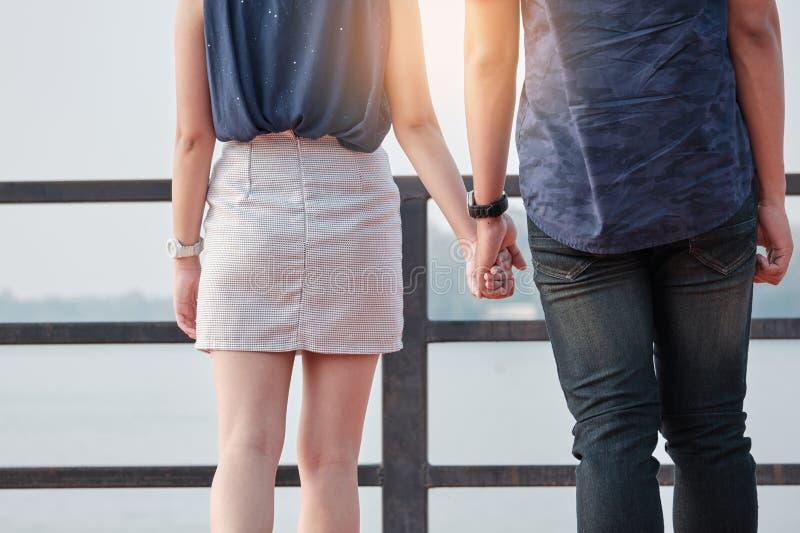 Pares asiáticos jovenes que colocan y que llevan a cabo la mano con amor puro foto de archivo libre de regalías