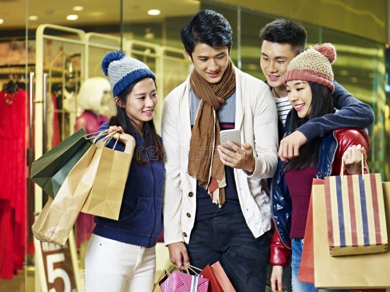 Pares asiáticos jovenes que disfrutan de hacer compras en alameda fotografía de archivo libre de regalías
