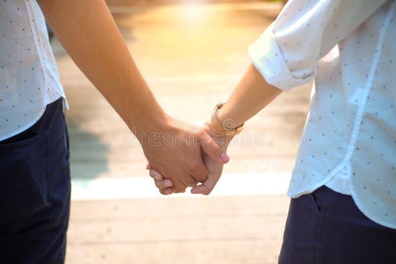 Pares asiáticos jovenes que llevan a cabo la mano con amor puro foto de archivo libre de regalías