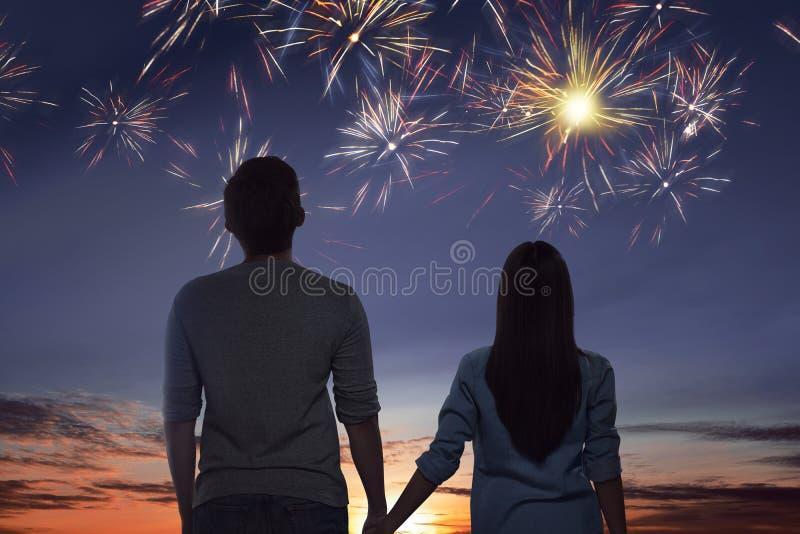 Pares asiáticos jovenes que miran los fuegos artificiales espectaculares fotos de archivo