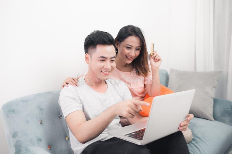 Pares asiáticos jovenes que practican surf en Internet y que hacen compras con el ordenador portátil Apartamento blanco moderno e fotos de archivo