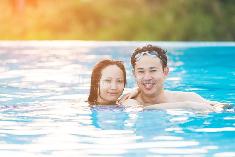 Pares asiáticos jovenes que se relajan en piscina fotografía de archivo