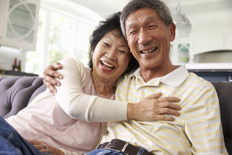 Pares asiáticos mayores en casa que se relajan en Sofa Together fotos de archivo