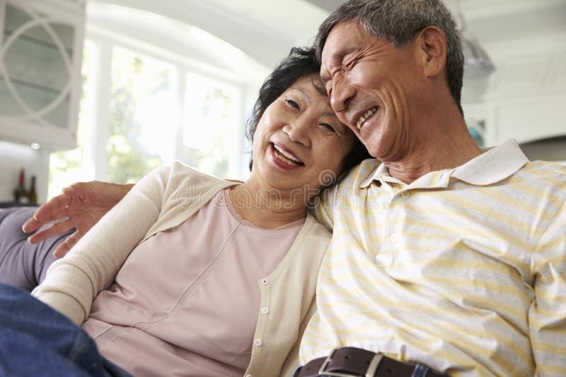 Pares asiáticos mayores en casa que se relajan en Sofa Together foto de archivo