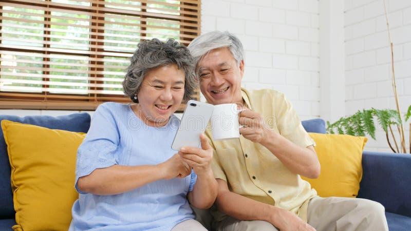 Pares asiáticos mayores felices usando el teléfono elegante mientras que se sienta en el fondo de la sala de estar del sofá en ca imagenes de archivo