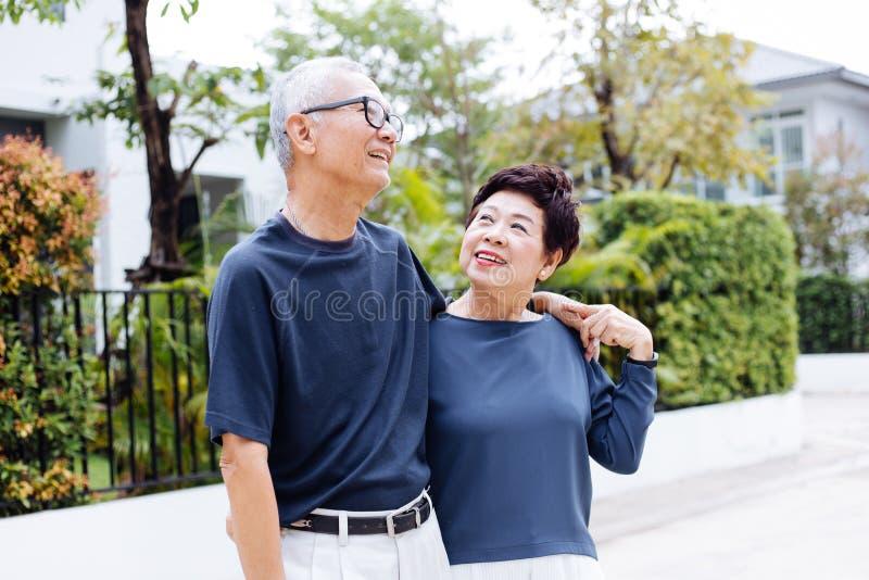 Pares asiáticos mayores jubilados felices que caminan y que miran uno a con romance en parque y casa al aire libre en fondo fotos de archivo