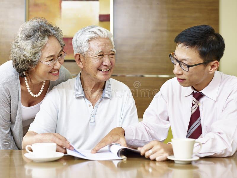 Pares asiáticos mayores que encuentran un representante de las ventas fotografía de archivo