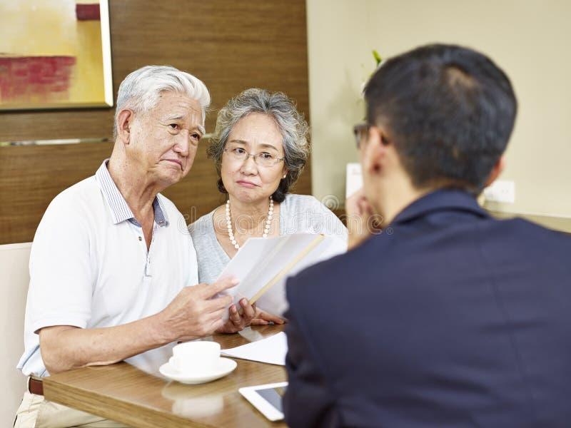 Pares asiáticos mayores que encuentran un representante de las ventas imagenes de archivo
