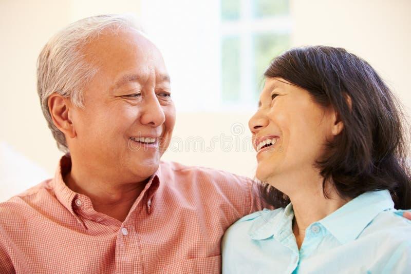 Pares asiáticos mayores que se sientan en Sofa At Home Together foto de archivo