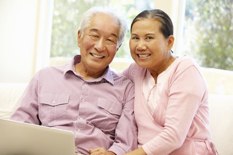 Pares asiáticos mayores usando el ordenador portátil fotos de archivo