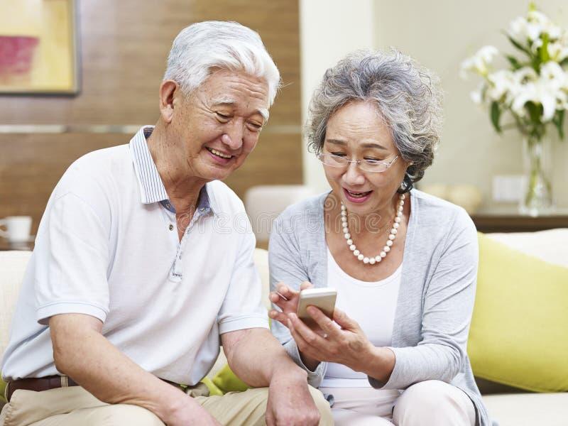 Pares asiáticos mayores usando el teléfono móvil en casa fotos de archivo